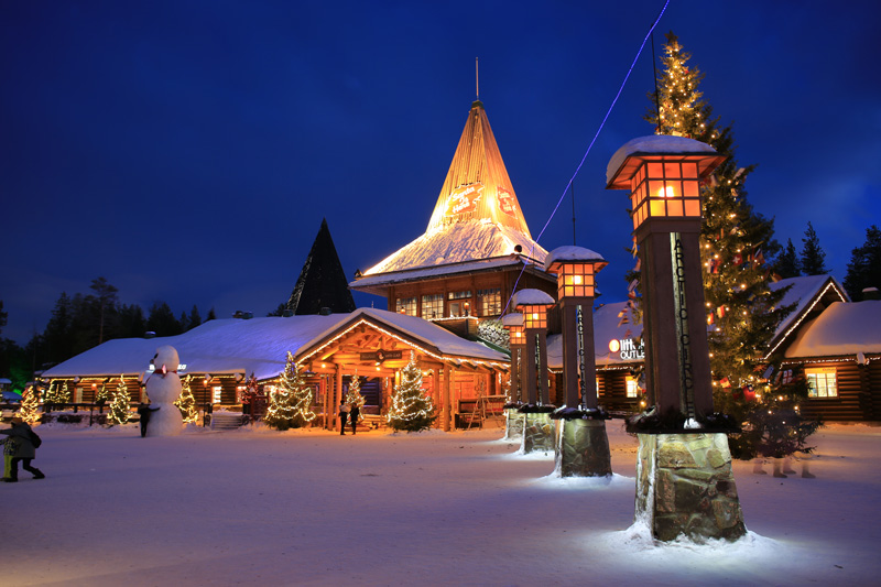 The snow-covered Santa Claus Village, in Santa's home town of Rovaniemi, gleams with brightly-lit buildings.