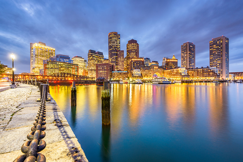 Boston's city skyline glitters in the harbour waters by dusk.