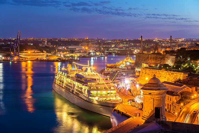 A twinkling port in historic Valletta, Malta, where a cruise ship docks for the evening.